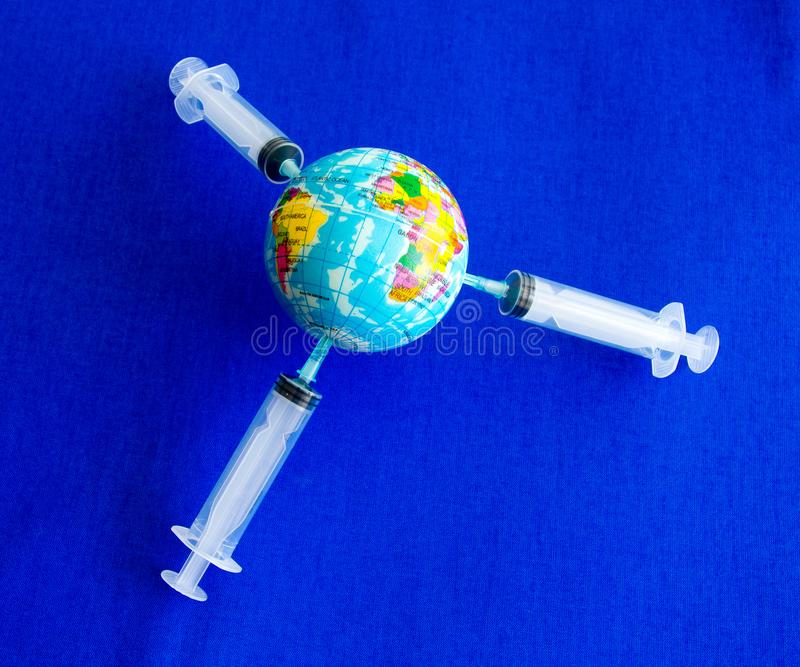 A terra modelo na seringa na imagem de fundo azul fotos de stock royalty free