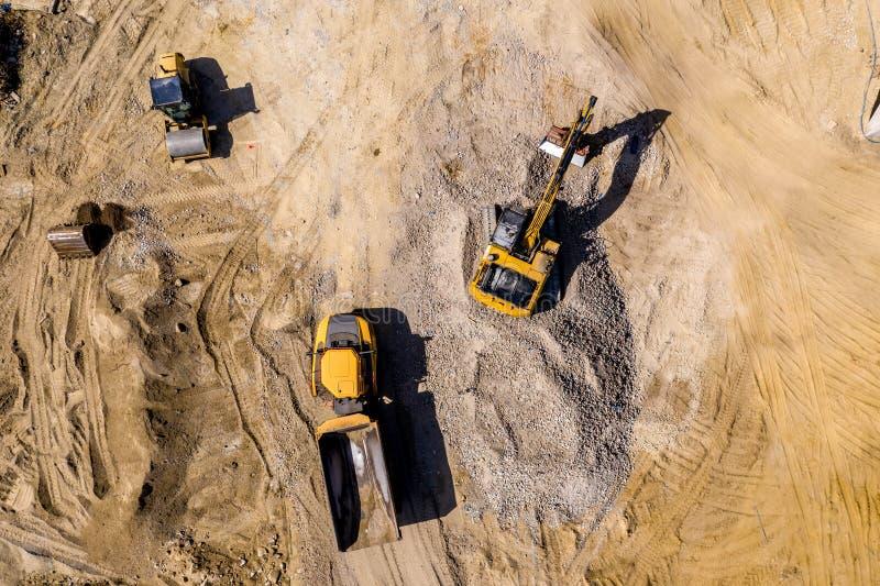 Terra muoventesi e scarico dell'escavatore del caricatore del camion industriale fotografia stock libera da diritti