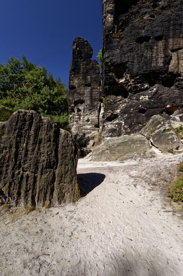 Terra sabbiosa leggera con le formazioni rocciose di hard rock alte che aumentano da  fotografie stock libere da diritti