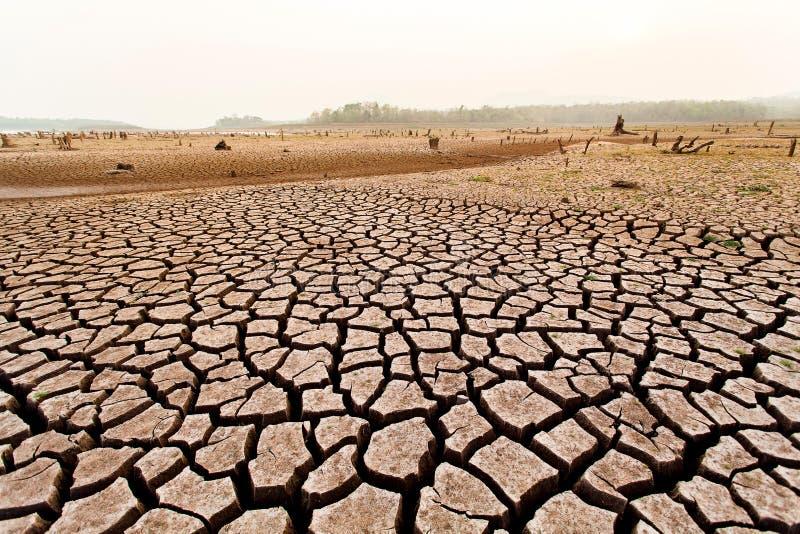 Terra seca rachada sem água abstraia o fundo imagens de stock