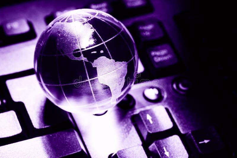 Terra trasparente del globo del mondo sulla tastiera di computer Concetto di affari delle comunicazioni globali Immagine colorata fotografie stock libere da diritti