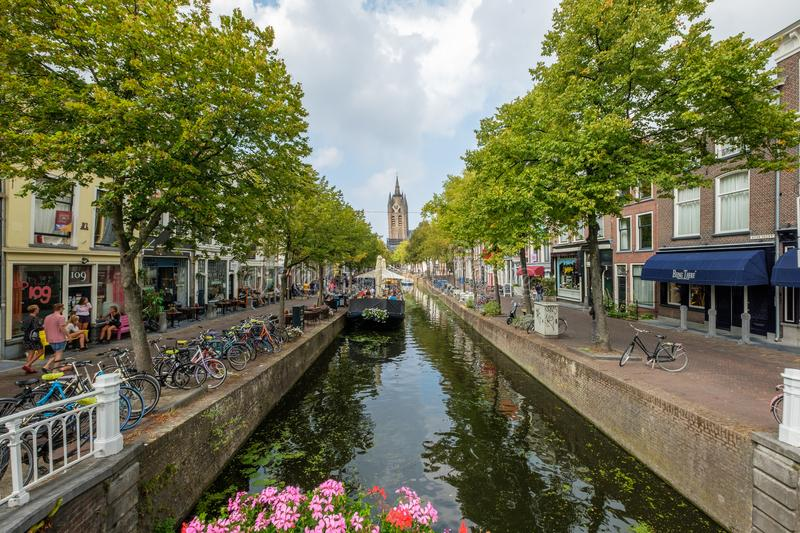 A terrace boat with happy people with a view of the leaning tower of the Oude Kerk in Delft, Netherlands royalty free stock photo