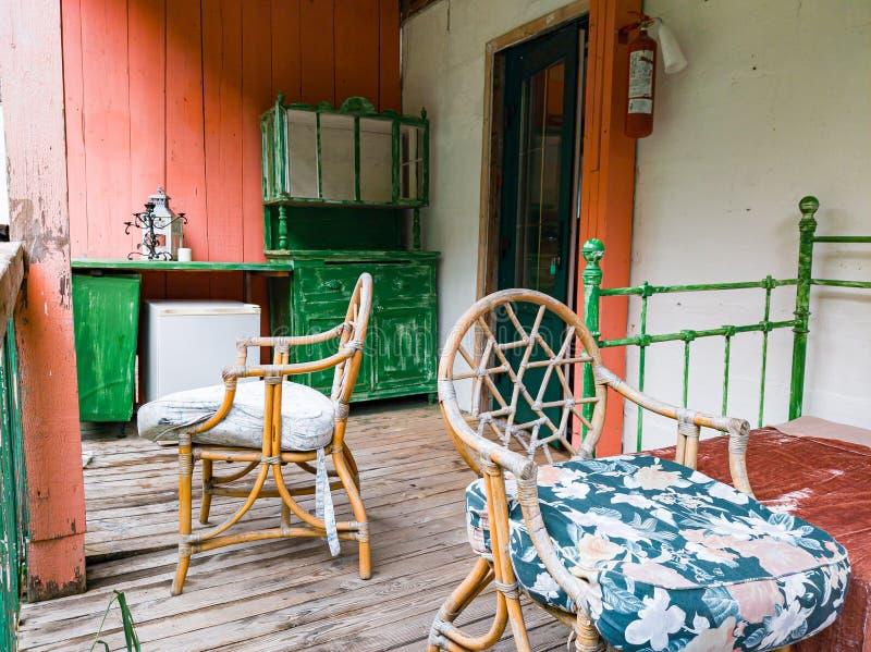 Terrace de uma casa de colheita com estólfos de madeira e corrimãos verdes e vermelhos perto de uma cama retrógrada Design de dec foto de stock