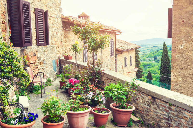 Terrace with flowers in an ancient italian house. Medieval town San Gimignano, Tuscany, Italy stock photo