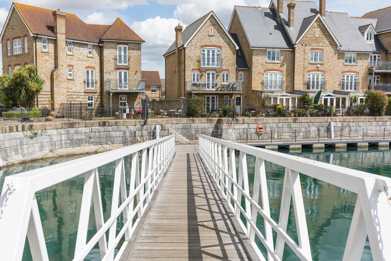 Terrace houses in Kent. Terrace, row, houses on St Mary's Island, Chatham, Kent. The houses are on the side of a dock and have a wooden footpath in front of them royalty free stock image
