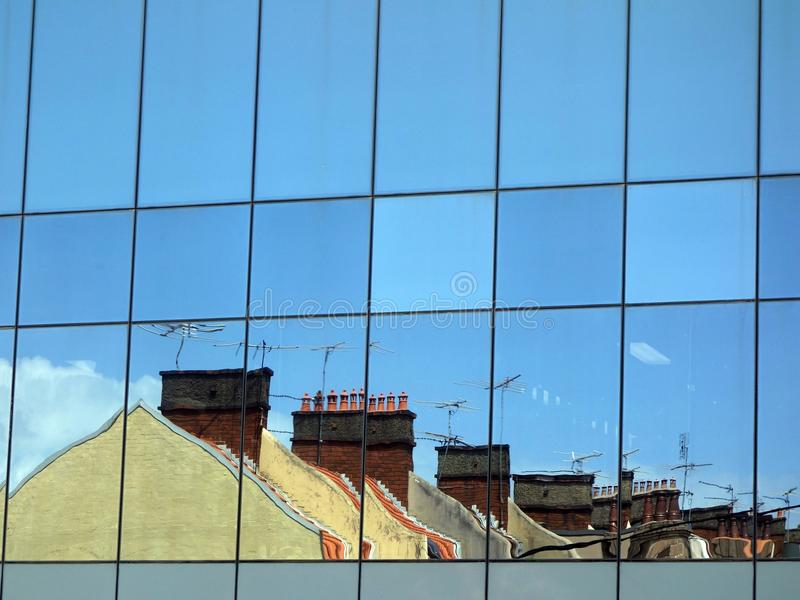 Terrace Houses. Old terrace houses reflected in glass facade of modern, new, office building stock image