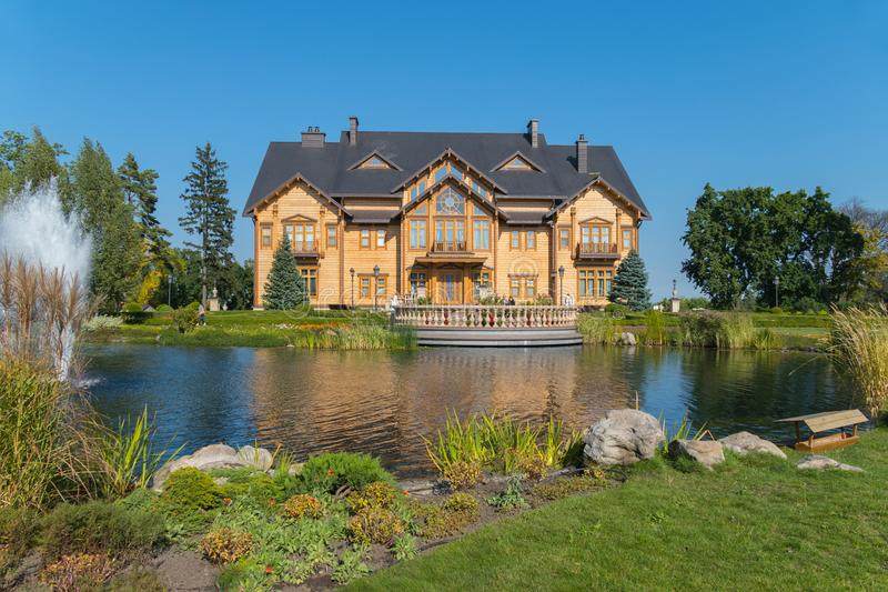 A terrace near the lake with a fountain in front of a luxurious wooden house. Mezhyhirya Ukraine stock photography