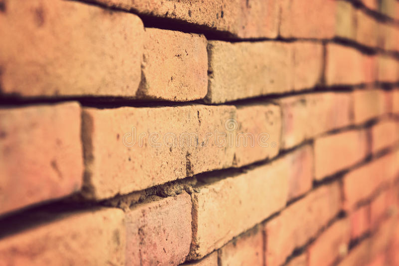 Terracotta brick wall in vintage retro color style. Terracotta brick wall shown in one point perspective with selective focus and shallow depth of field, in royalty free stock images