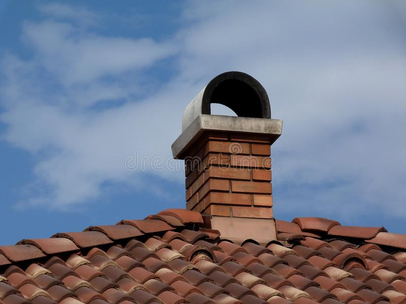 Terracotta clay roof tiles and brick chimney. Modern brick chimneys with arched concrete cap stone, terracotta clay roof tiles & clay vents under blue sky on royalty free stock image