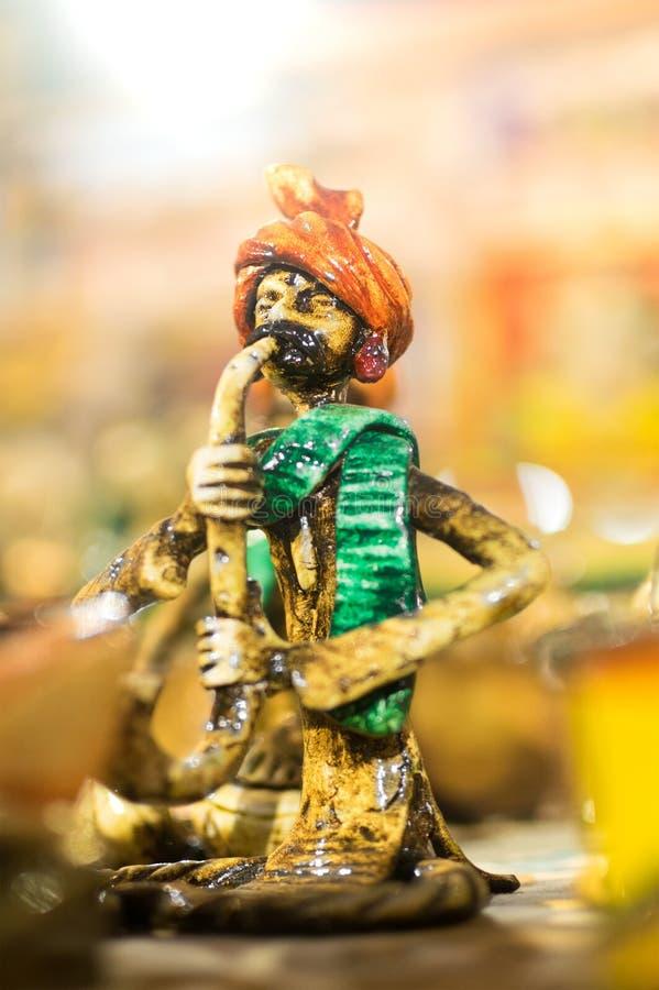 Terracotta doll, snake charmer, Indian handicrafts. KOLKATA, WEST BENGAL , INDIA - NOVEMBER 23RD 2014 : Terracotta doll, snake charmer, handicraft on display stock photos