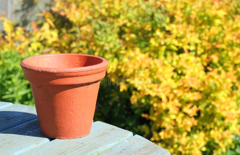Terracotta flower pot. An empty terracotta flower pot on a wooden table with a background of bushes stock images