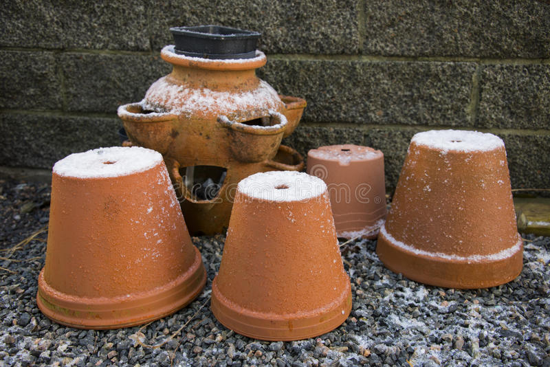 Terracotta pots in winter. Garden terracotta pots covered in ice and snow royalty free stock photo