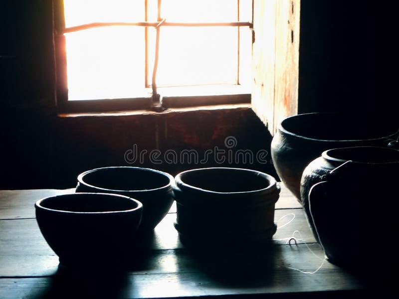 Terraglie su una tavola di legno dalla finestra fotografie stock libere da diritti