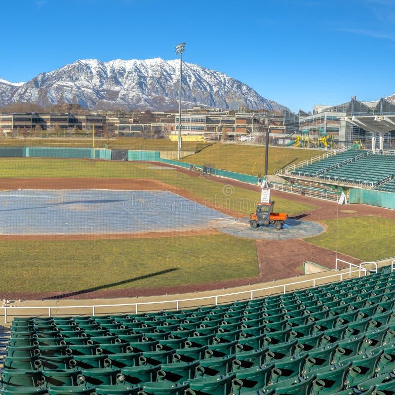 Terrain de base-ball carré clair avec l'allocation des places à gradins verte contre la montagne et le ciel bleu vibrant photo libre de droits