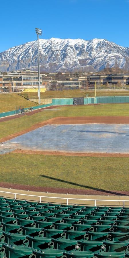 Terrain de base-ball vertical clair avec l'allocation des places ? gradins verte contre la montagne et le ciel bleu vibrant photos libres de droits