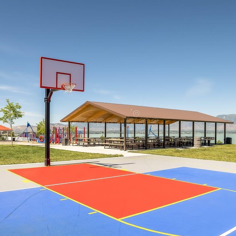 Terrain de basket extérieur de place avec un pavillon et un terrain de jeu de pique-nique à l'arrière-plan image libre de droits