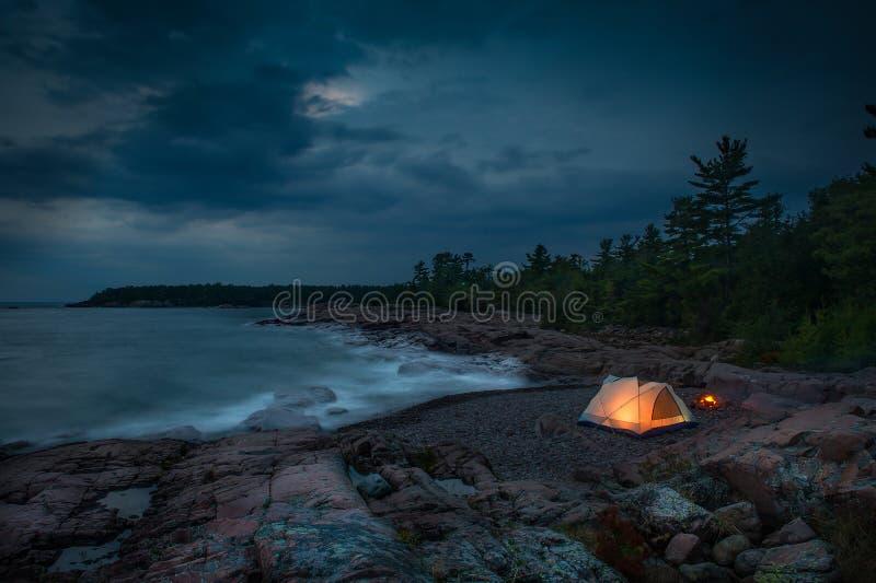 Terrain de camping rougeoyant par l'eau photos stock