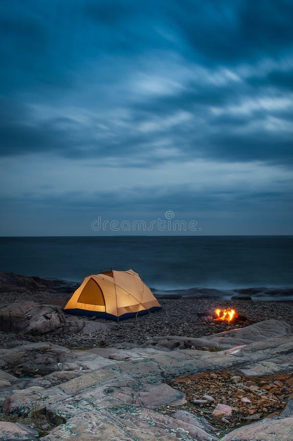 Terrain de camping rougeoyant par l'eau image stock