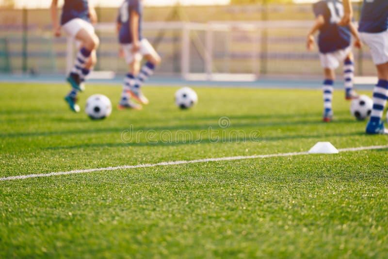 Terrain de football brouill? ? l'?cole Jeunes footballeurs s'exer?ant sur le lancement images stock