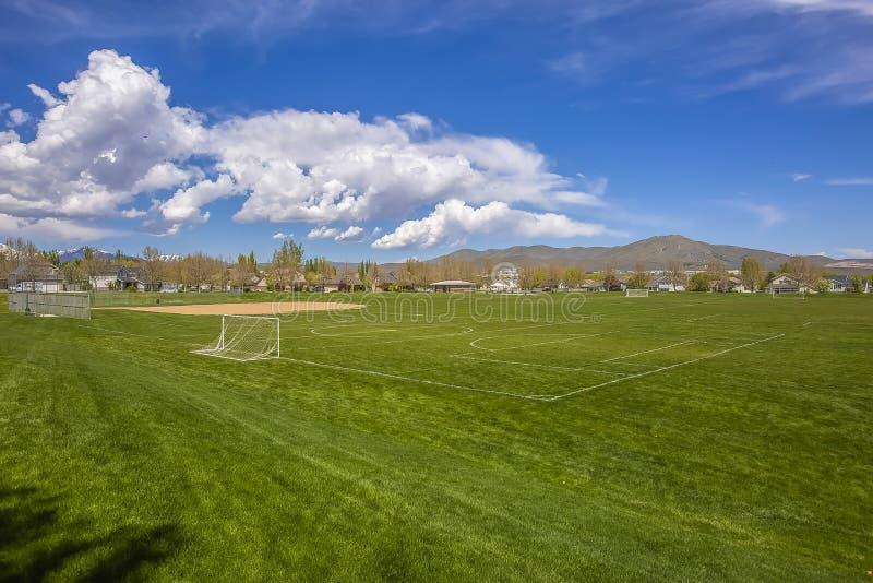 Terrain de football et terrain de base-ball avec la vue de la montagne et du ciel bleu nuageux photographie stock libre de droits
