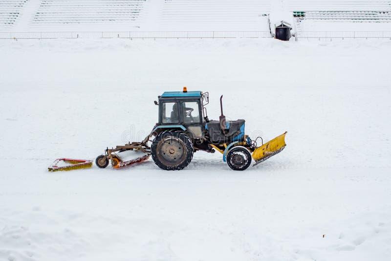 Terrain de football lancé des boules de neige par tracteur de nettoyage image stock