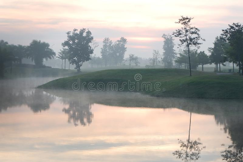 Terrain de golf avec brumeux pendant le matin photographie stock libre de droits