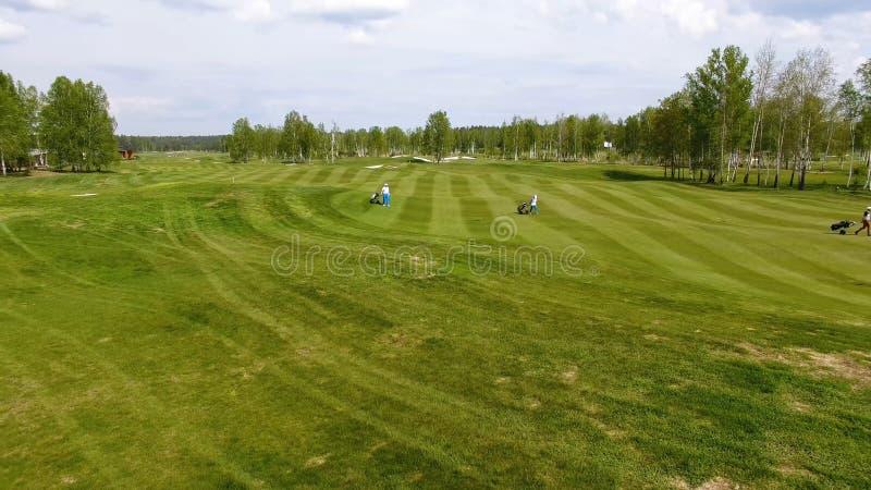 Terrain de golf de vue aérienne Golfeurs descendant le fairway sur un cours avec le sac et le chariot de golf image libre de droits