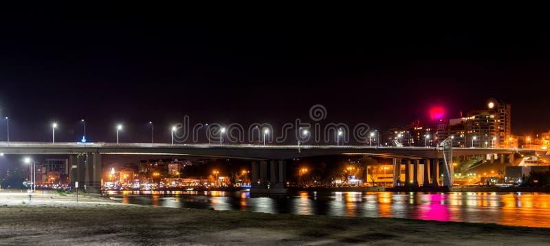 Terrain de jeu sur la plage sablonneuse Pont au-dessus de la rivière et de la ville de nuit sur le fond images libres de droits