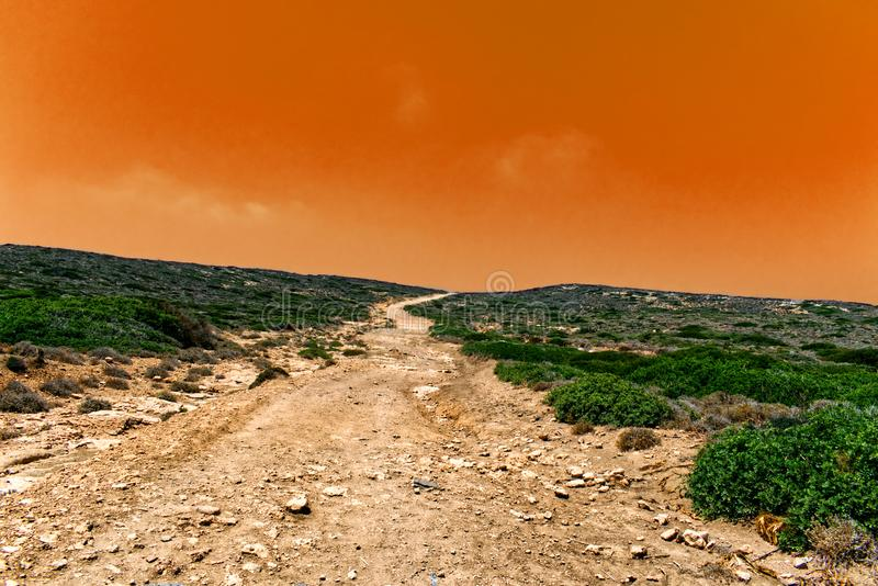 Terrain journey in the wilderness with orange sky stock images