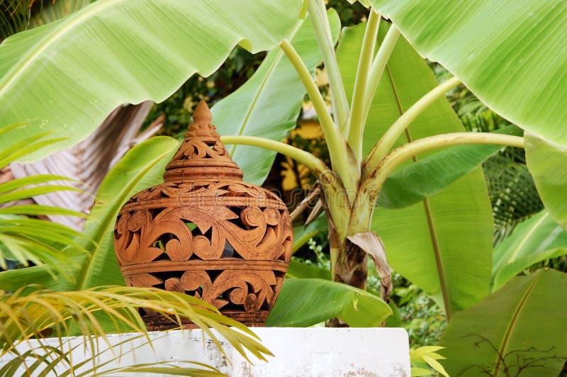 Terrakottalampenschirm unter der Bananenstaude stockfoto