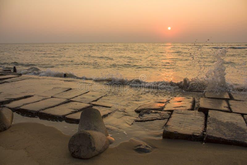 Terraplén concreto y el pegarse tetrápodo fuera de la arena amarilla contra el contexto de salpicar olas oceánicas bajo tarde fotos de archivo libres de regalías