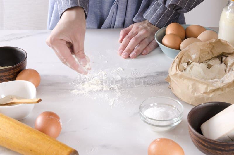 Terraplén de la bolsa de papel de la harina, huevos, sal, levadura, rodillo, toalla de cocina en la tabla blanca Proceso de la pr fotografía de archivo libre de regalías