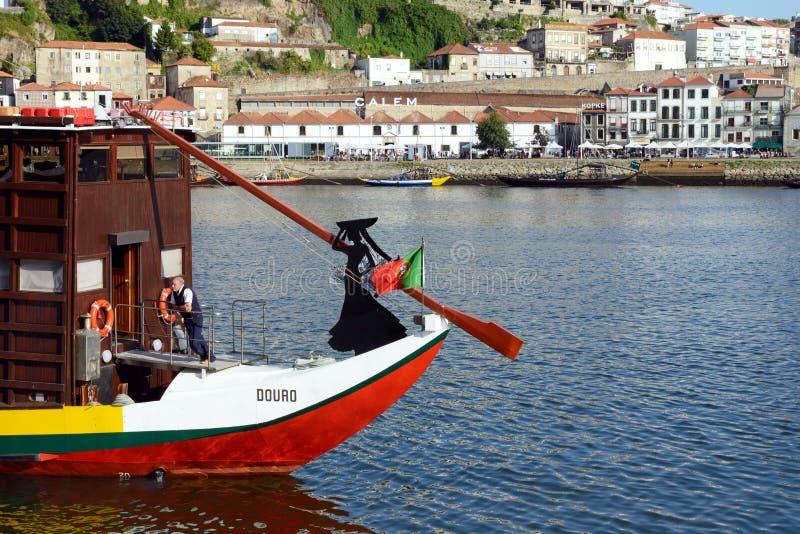 Terraplén del río del Duero Silueta de una mujer y la bandera de Portugal en el arco de un barco de madera imágenes de archivo libres de regalías