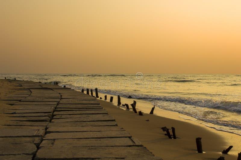 Terraplenagem concreta com as colunas de madeira velhas que colam fora da areia amarela na perspectiva das ondas de oceano sob a fotos de stock royalty free