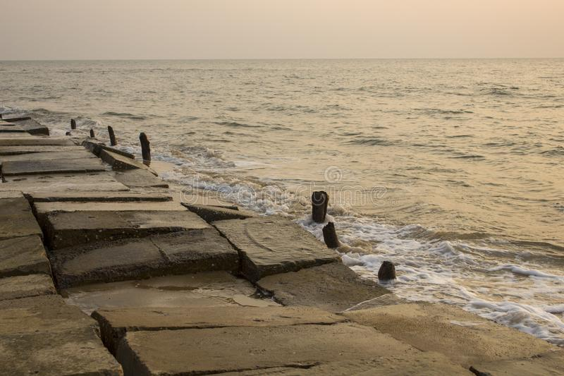 Terraplenagem concreta destruída velha com as colunas de madeira que projetam-se da água na perspectiva das ondas de oceano no imagens de stock royalty free