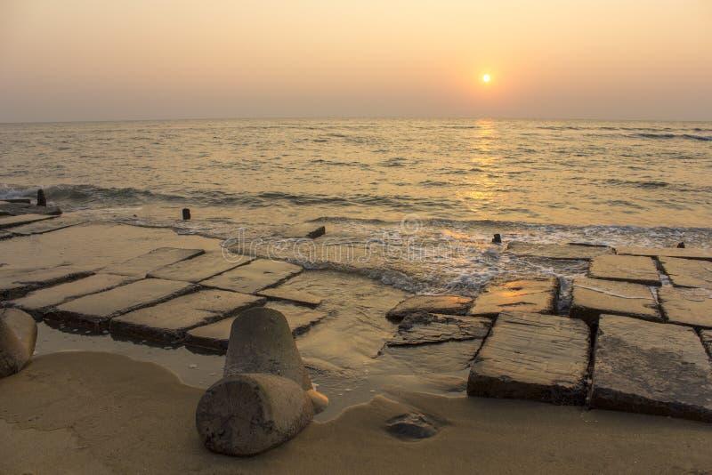 Terraplenagem concreta destruída velha com tetrapods na areia contra o céu de nivelamento e o sol sobre o oceano imagens de stock