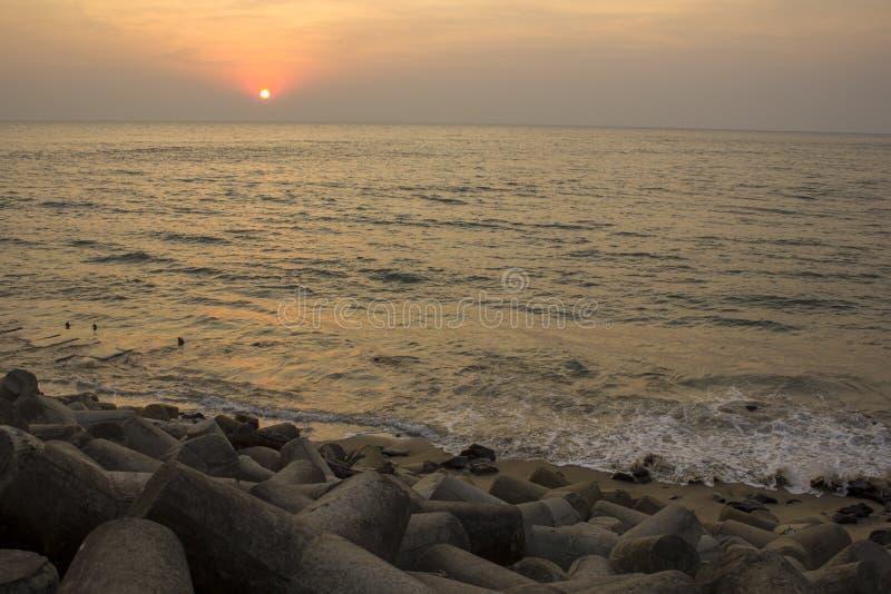Terraplenagem concreta do mar velho com tetrapods na perspectiva das ondas de oceano sob o céu brilhante do por do sol fotos de stock royalty free