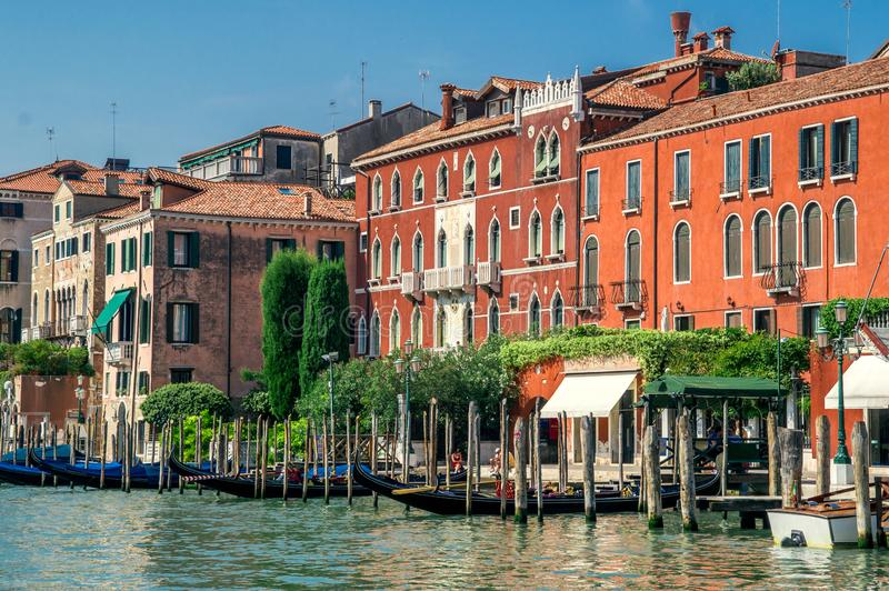 Terraplenagem pitoresca de Grand Canal em um dia de verão ensolarado Casas Venetian brilhantes na água, coberto de vegetação com  fotos de stock royalty free