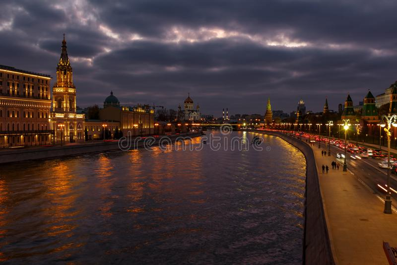 Terraplenagens do rio de Moskva contra o Kremlin de Moscou em um fundo do céu nebuloso na noite Paisagem da cidade imagem de stock