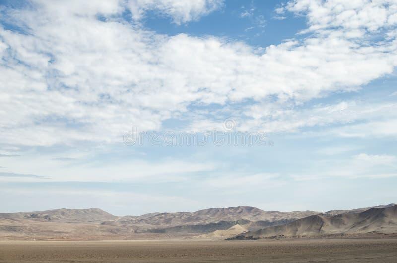 Terras áridas do deserto sob o céu nebuloso azul imagens de stock royalty free