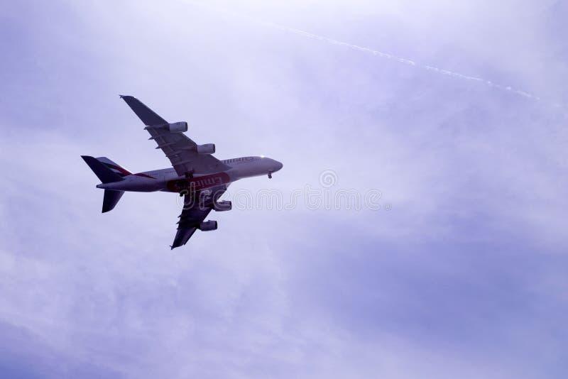 Terras cinzentas grandes do avião de passageiros do passageiro de Emirates Airlines Avião em um embaçamento azul contra o céu foto de stock royalty free
