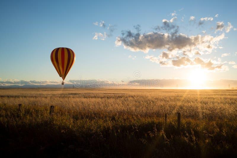 Terras do por do sol e de um balão de ar quente no canola em pradarias de Alberta fotografia de stock