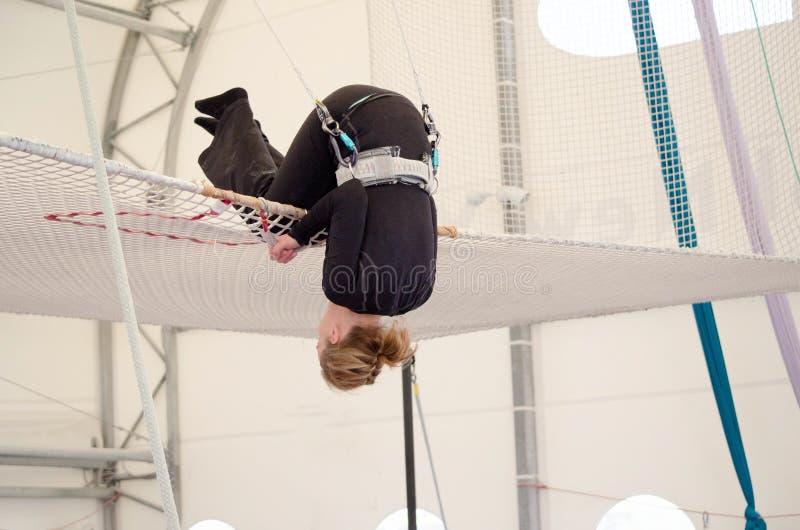 Terras fêmeas adultas em uma rede, preparando-se para desmontar na em uma escola de voo do trapézio em um gym interno A mulher é  imagem de stock