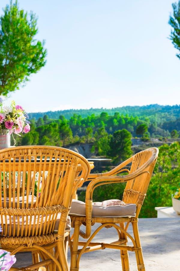 Terrass av den lyxiga vita villan med buketten för blommor för tabell för gnäggandestolar på tabellen som fascinerar sikt av dalb royaltyfria bilder