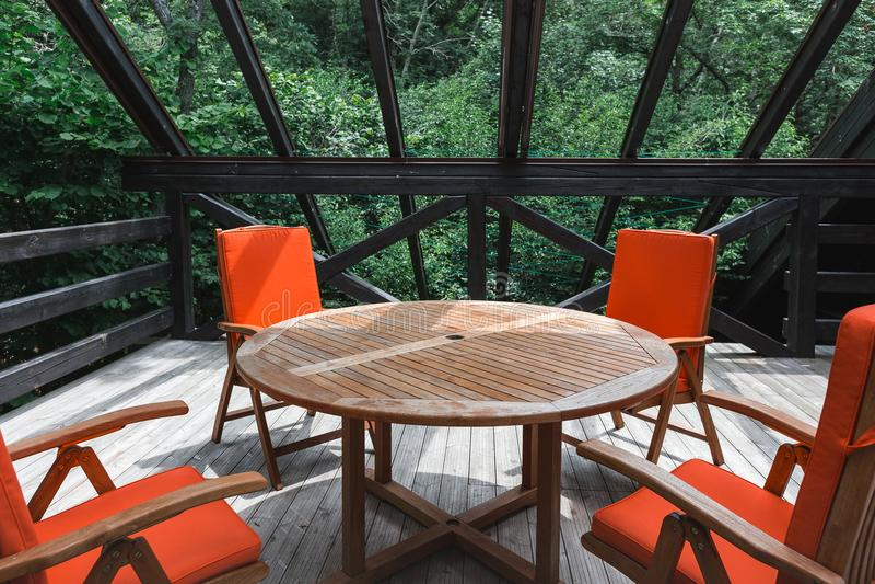 Terrasse de pays d'été avec une table et des chaises oranges le beau plan rapproché détaille le cru intérieur de table de plaque  photographie stock