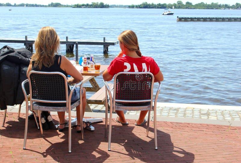 Terrasse der jungen Frau trinkt See, Loosdrecht, die Niederlande stockfotografie