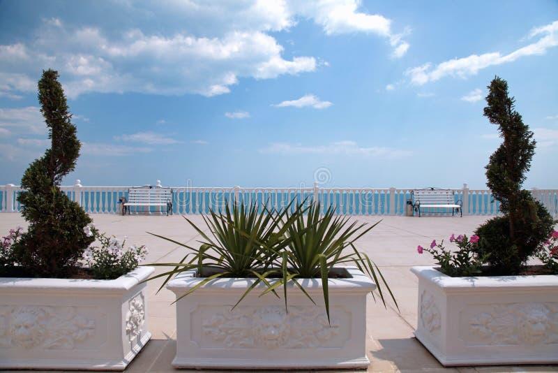 Terrasse donnant sur la mer, la balustrade blanche, le banc et le buis photo libre de droits
