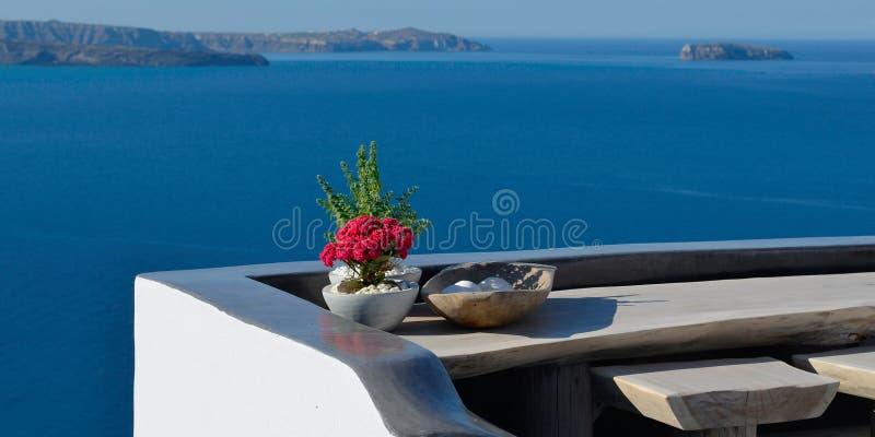 Terrasse panoramique avec la fleur rouge sur la table Négligence de la caldeira à Oia, Santorini, Grèce image stock