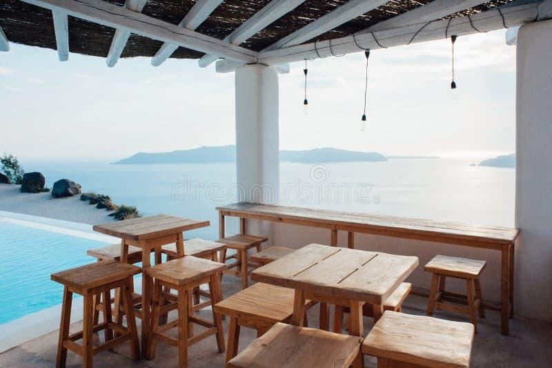 Terrasse unter dem Dach mit den Holztischen und Stühlen, die das Meer nahe bei dem Swimmingpool in Santorini übersehen stockfotos