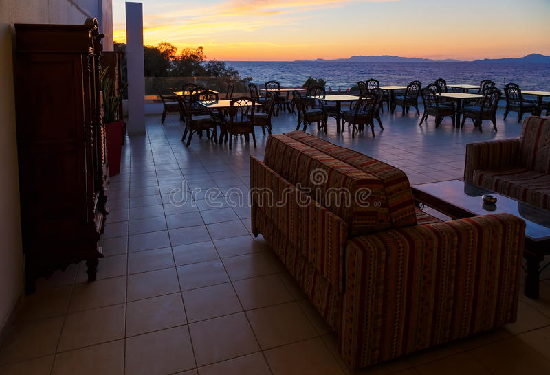 Terrasse von Restaurantglastischen mit Seeansicht und schönem Sonnenuntergang stockbilder